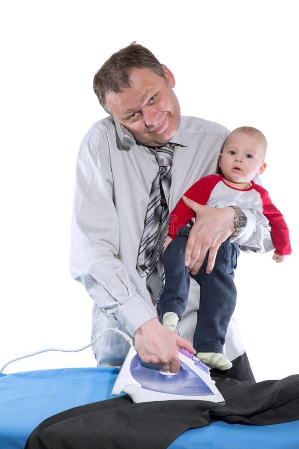L'homme repasse, parle du téléphone et tient le bébé photos libres de droits