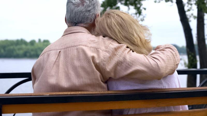 L'homme retiré étreignant l'épouse s'asseyant sur le banc de parc près de la rivière, les couples supérieurs se reposent photographie stock
