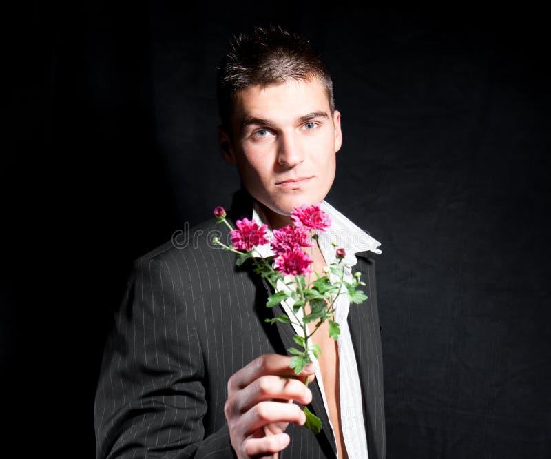 L'homme romantique est des fleurs de fixation au femme image libre de droits