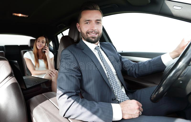 L'homme sérieux élégant attirant conduit la bonne voiture images libres de droits