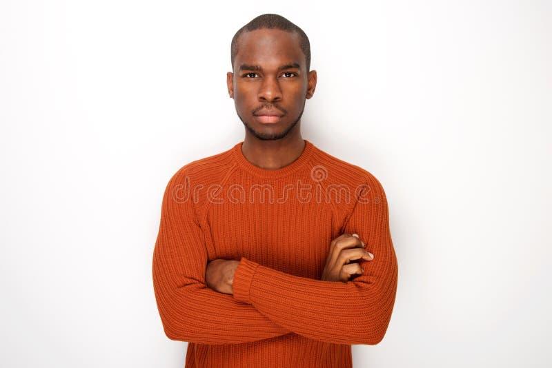 L'homme sérieux d'afro-américain avec des bras a croisé la pose sur le fond blanc d'isolement photos stock