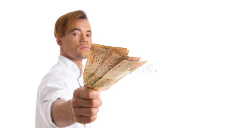L'homme sérieux livre l'argent Le jeune homme de couleur est dans le cuisinier blanc uni images stock