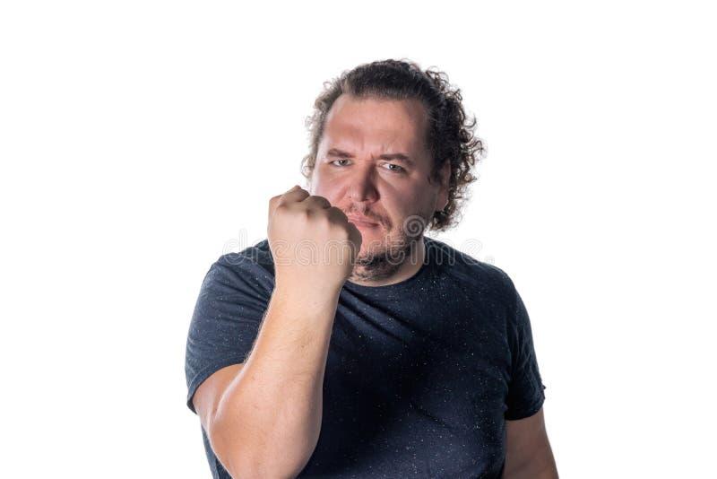 L'homme sérieux montre le poing serré de geste, regardant la caméra, vue de face, d'isolement photos libres de droits
