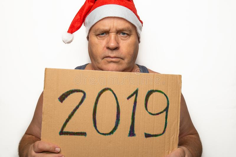 L'homme sérieux supérieur drôle dans le chapeau rouge de Santa Claus Christmas tient le carton avec 2019 nombres dans des mains e photographie stock