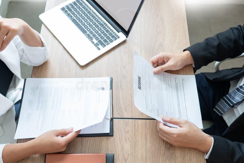 L'homme sérieux a une réunion d'affaires lisant un résumé au sujet de décision de location pendant une entrevue d'emploi à la soc photographie stock