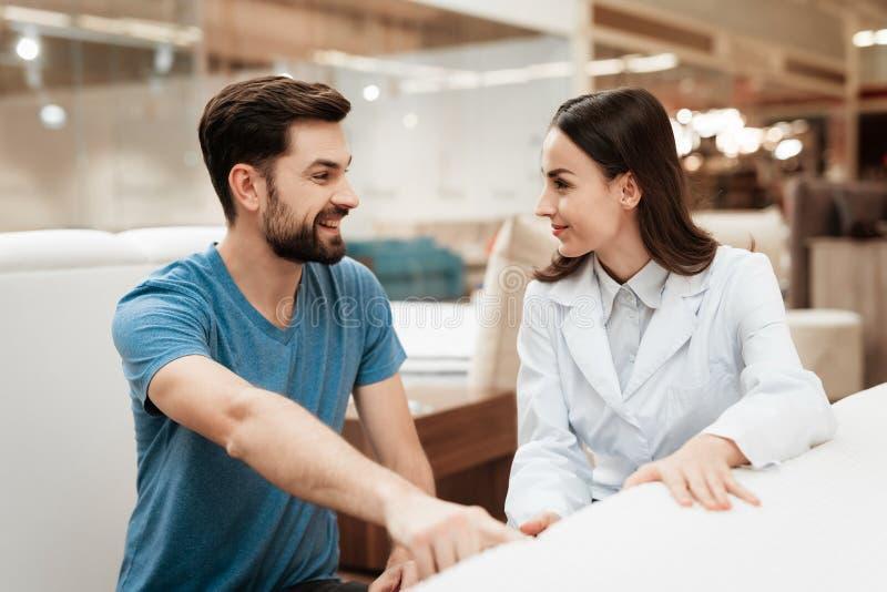 L'homme sûr avec la barbe communique avec le beau consultant en matière de fille dans le magasin de matelas images stock