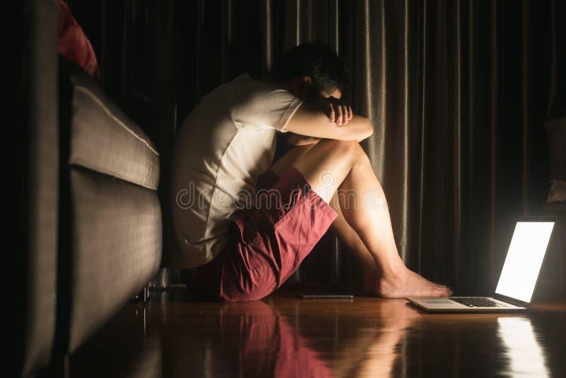 L'homme s'asseyent sur le smartphone d'utilisation de plancher et la douleur d'ordinateur portable du désordre de derpression, co photographie stock