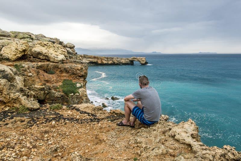 L'homme s'assied au bord d'une falaise et des regards dans la distance en mer image stock