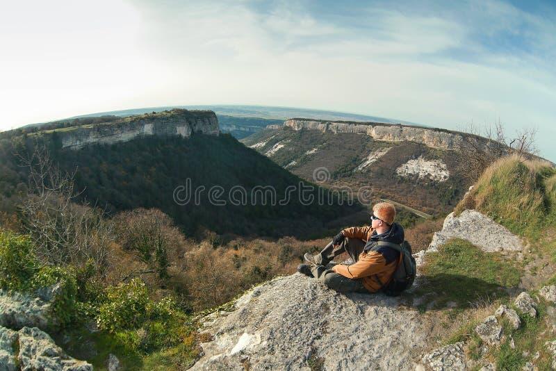 L'homme s'assied au bord d'une falaise sur le plateau de Mangup photo stock