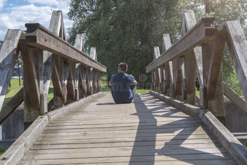 L'homme s'assied avec le sien de retour a tourné sur un vieux pont en bois image stock