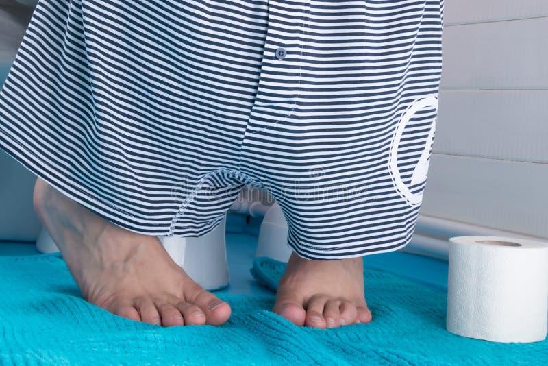 L'homme s'assied dans la toilette avec les sous-vêtements et le papier hygiénique enlevés en cas d'empoisonnement, plan rapproché images stock