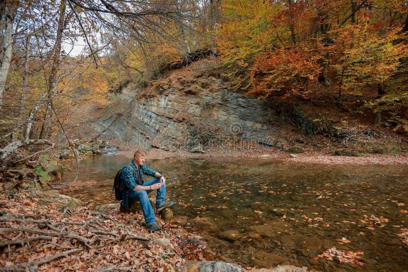 L'homme s'assied près du courant de montagne en automne image libre de droits