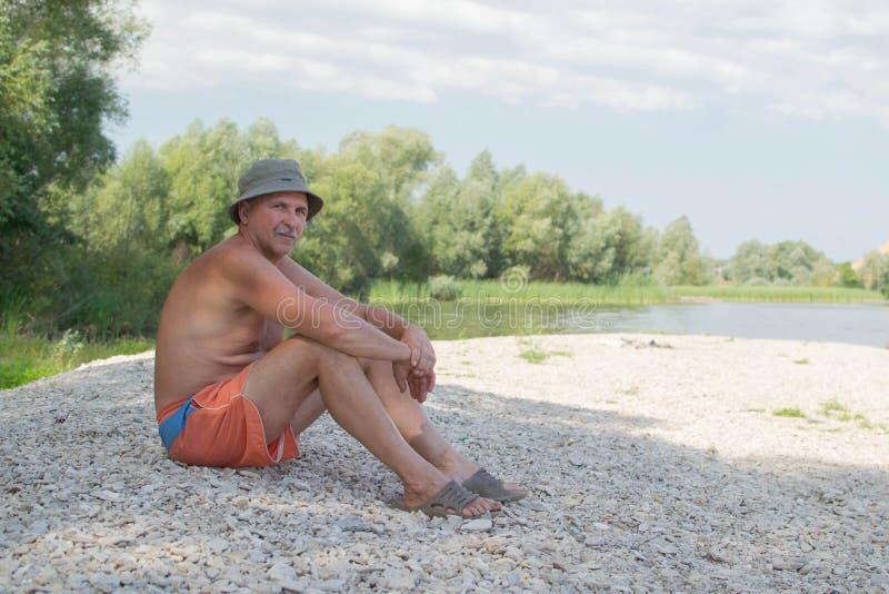 L'homme s'assied sur la banque de la rivière photos libres de droits