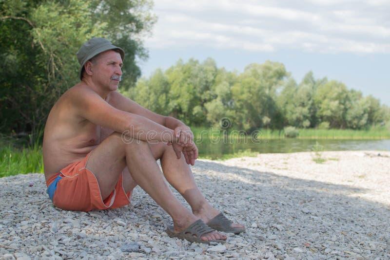 L'homme s'assied sur la banque de la rivière images libres de droits