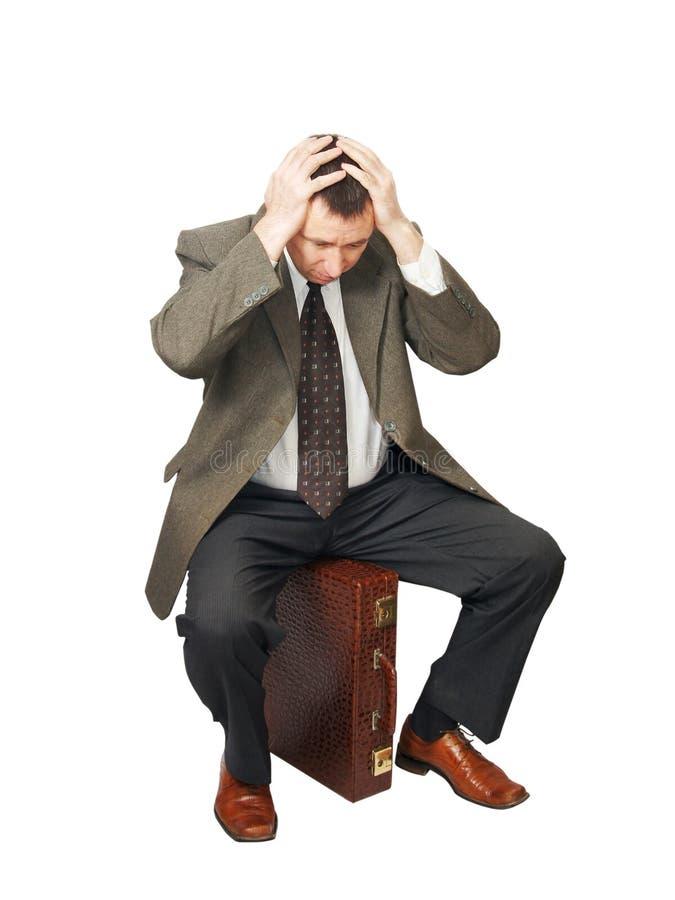 L'homme s'assied sur le sac et les mains saisies pour la tête photographie stock