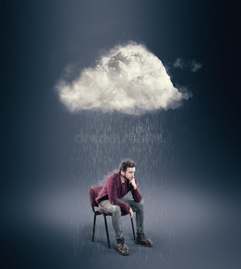 L'homme s'assied sur une chaise et pense avec un nuage au-dessus de sa tête photographie stock