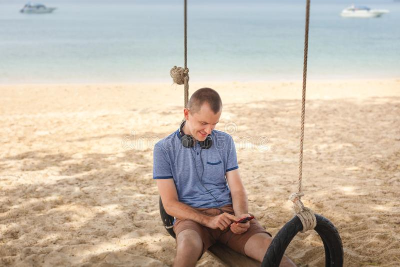 L'homme s'assied sur une oscillation et écoute la musique Concept de mode de vie La Thaïlande, Krabi Février 2017 photos libres de droits