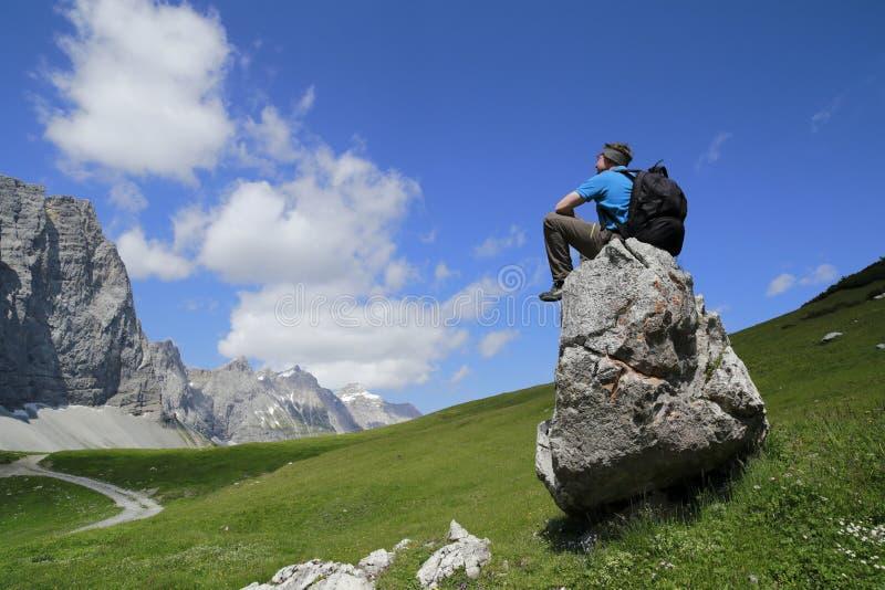 L'homme s'assied sur une pierre photo stock