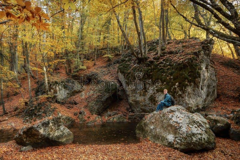 L'homme s'assied sur une pierre pr?s d'un courant en automne images libres de droits