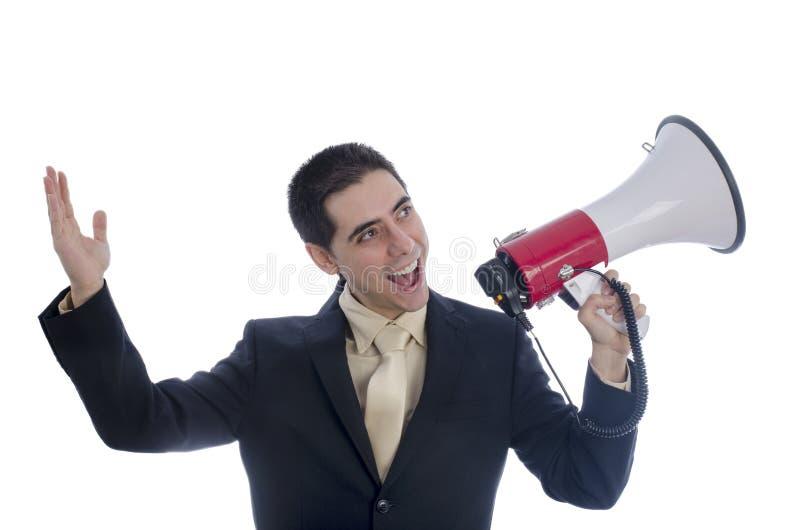 L'homme s'est habillé dans le costume et le lien criant par le mégaphone image libre de droits