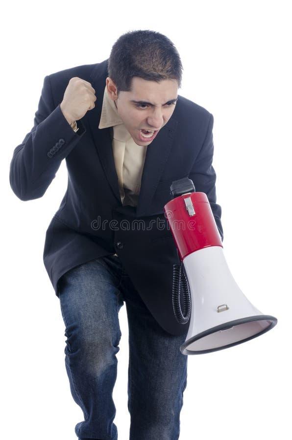 L'homme s'est habillé dans le costume et le lien criant par le mégaphone images libres de droits