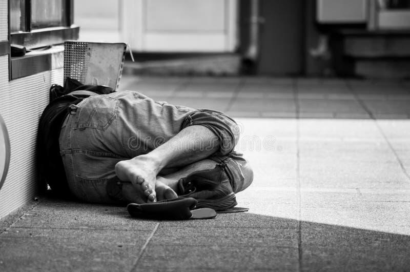 L'homme sans abri dort sur la rue, dans l'ombre du bâtiment photo stock
