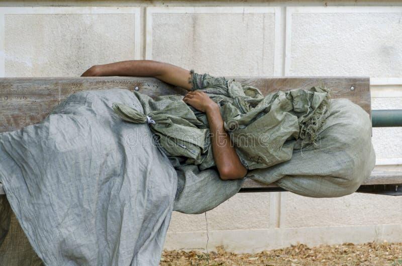 L'homme sans abri dort sur un banc image libre de droits