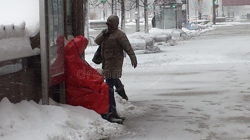 L'homme sans abri a trouvé l'abri à l'arrêt d'autobus pendant la tempête de neige photos libres de droits