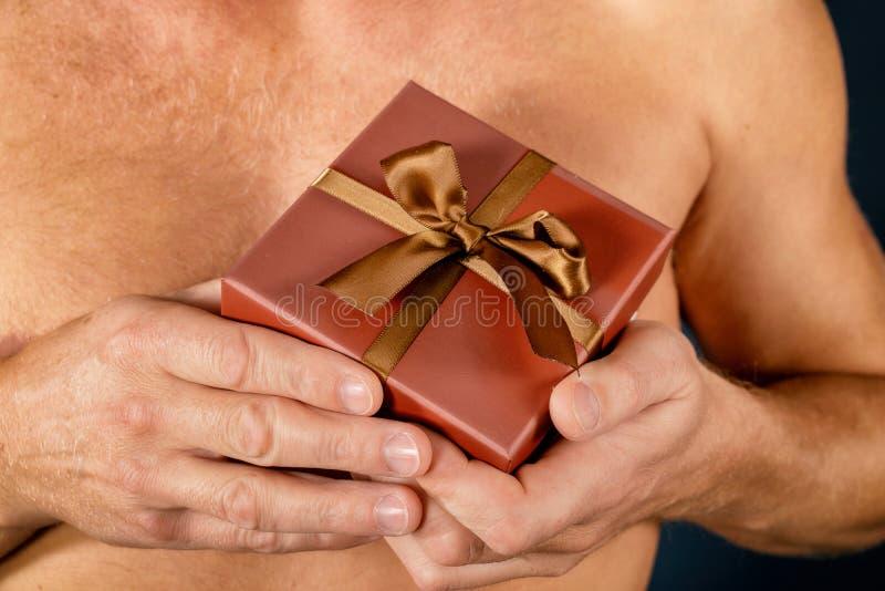 L'homme sans chemise juge un boîte-cadeau d'isolement sur le blanc surprise Projectile de studio Vacances et occasion spéciale images libres de droits