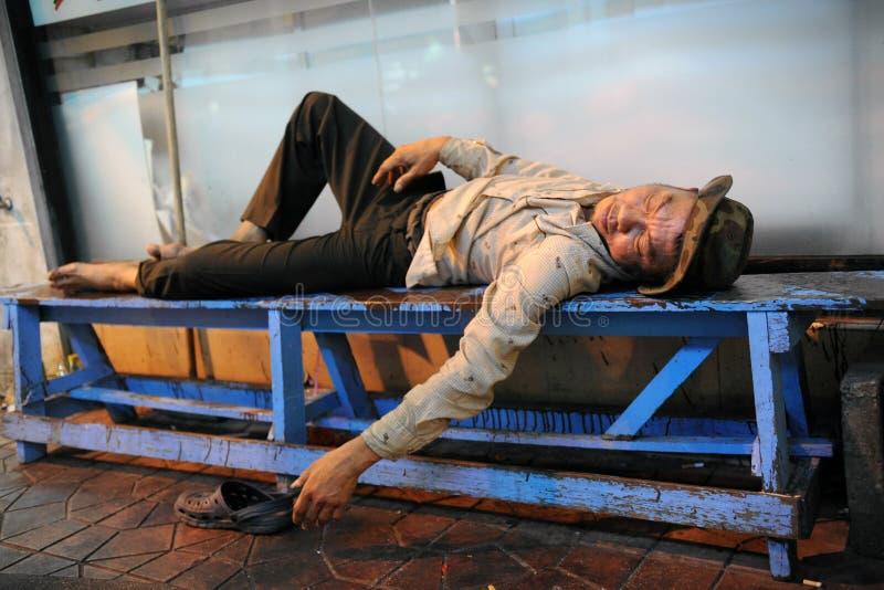 L'homme sans foyer dort sur la rue image stock