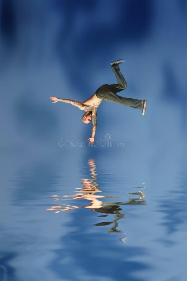 L'homme sautant dans l'eau photo libre de droits