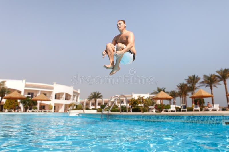 L'homme sautant dans la piscine photo stock
