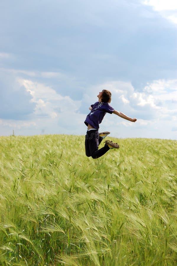 L'homme sautant dans le domaine de blé image stock