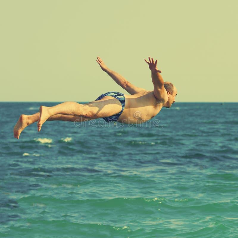L'homme sautant en mer image libre de droits