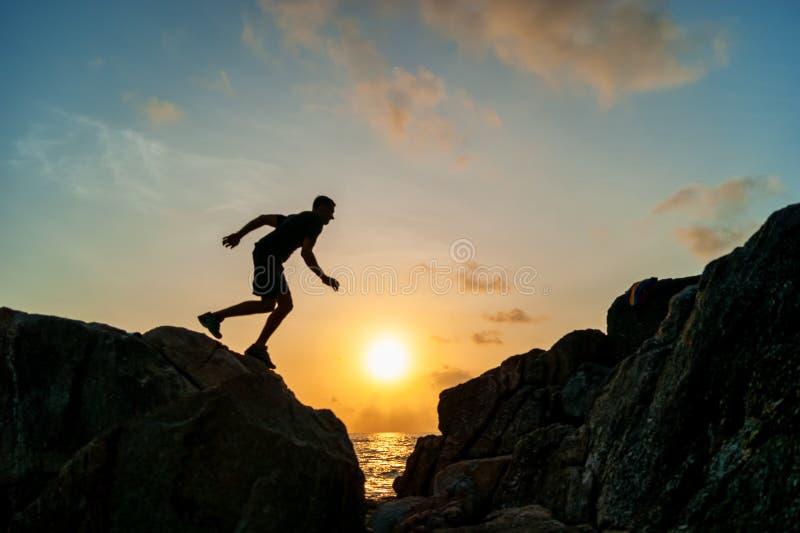 L'homme sautant sur des roches au lever de soleil photographie stock libre de droits
