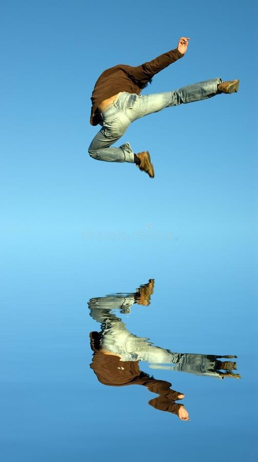 L'homme sautant sur l'eau photo stock