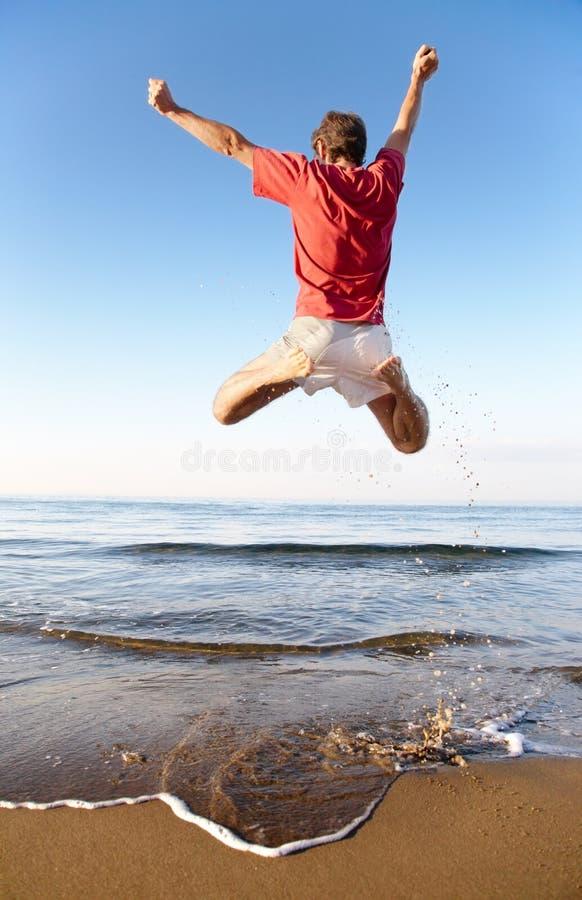L'homme sautant sur la plage images libres de droits