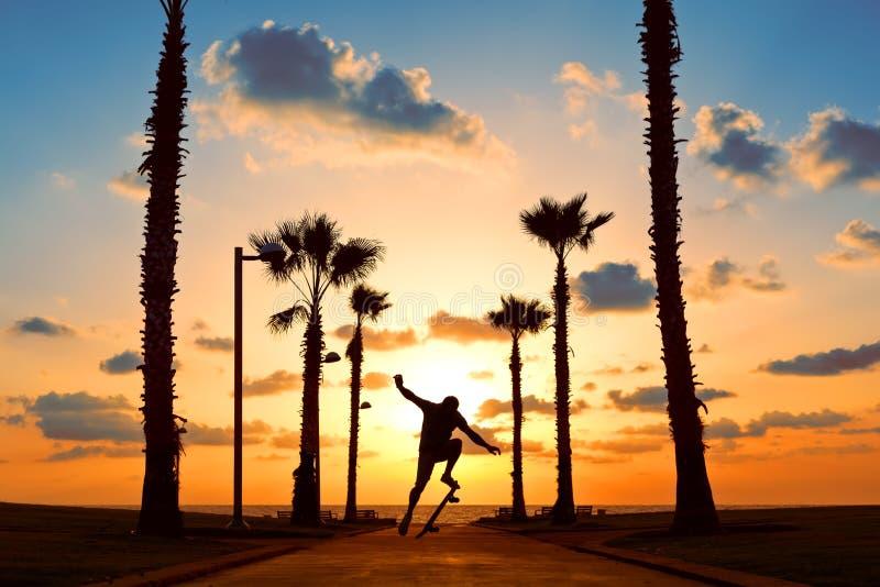 L'homme sautant sur la planche à roulettes dans le coucher du soleil photo libre de droits
