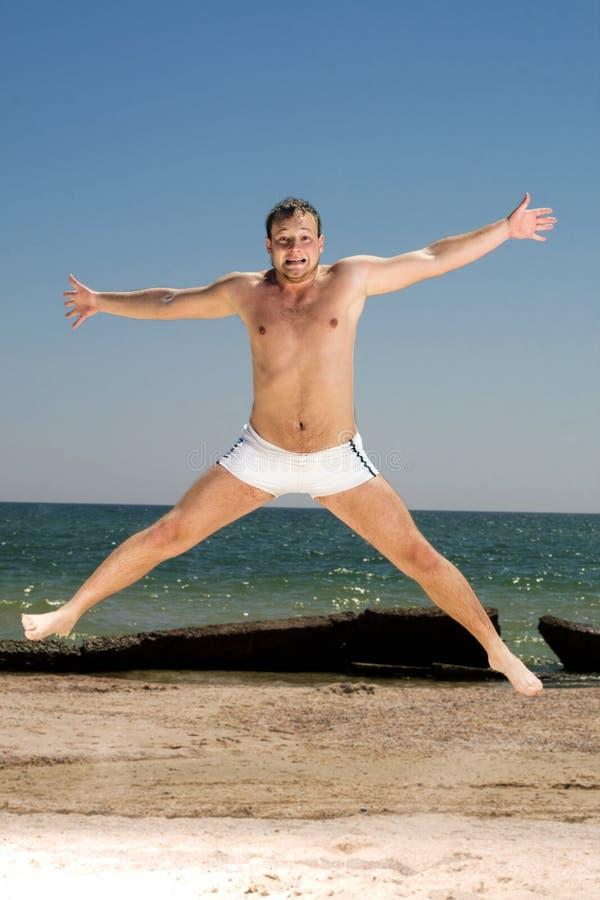 L'homme sautant sur une plage image libre de droits