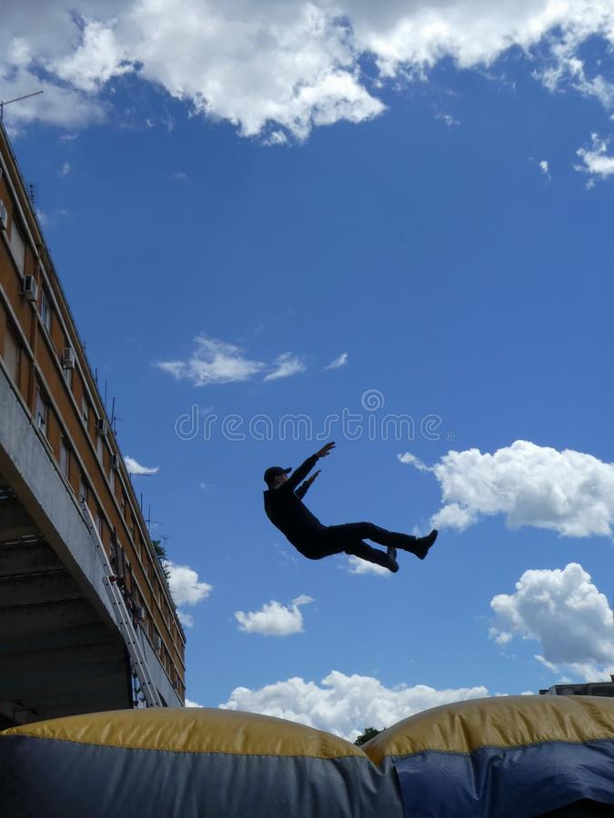 L'homme sautant vers le bas au coussin gonflable de délivrance également connu sous le nom de coussin de saut ou coussin d'air photo stock