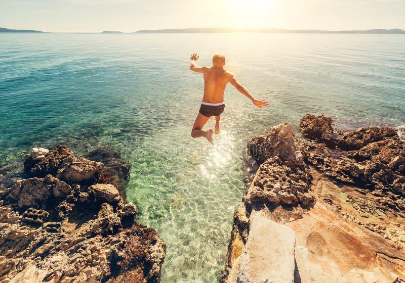 L'homme saute dans l'eau bleue de lagune de mer photographie stock