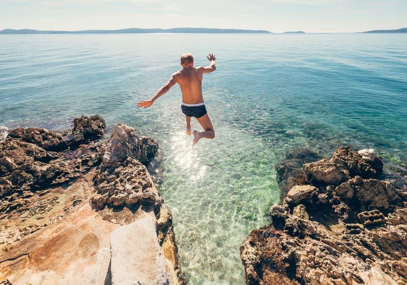 L'homme saute dans l'eau bleue de lagune de mer photographie stock libre de droits