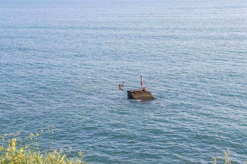 L'homme saute dans le saut périlleux arrière bleu de mer photo libre de droits