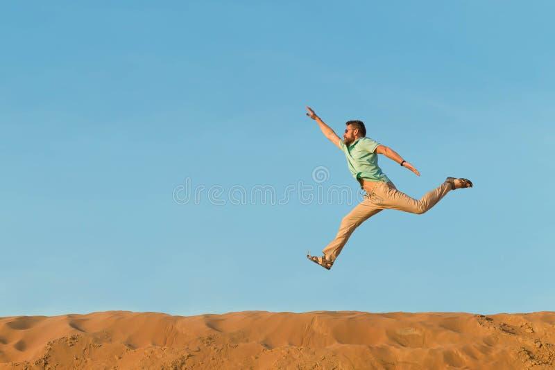 L'homme saute par-dessus des crêtes des dunes dans le désert sous le soleil passionné haut La main droite est hig images stock