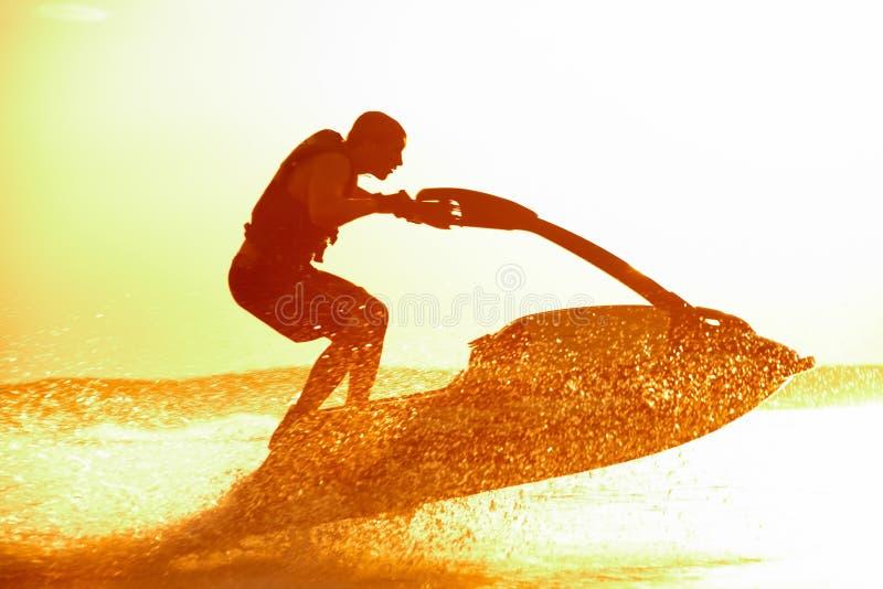 L'homme saute sur le jetski photographie stock libre de droits