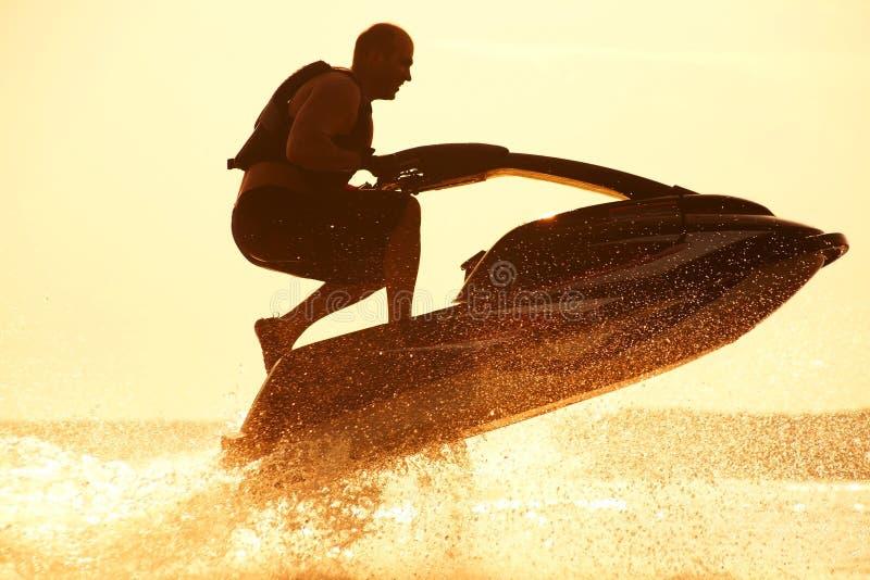 L'homme saute sur le jetski image stock