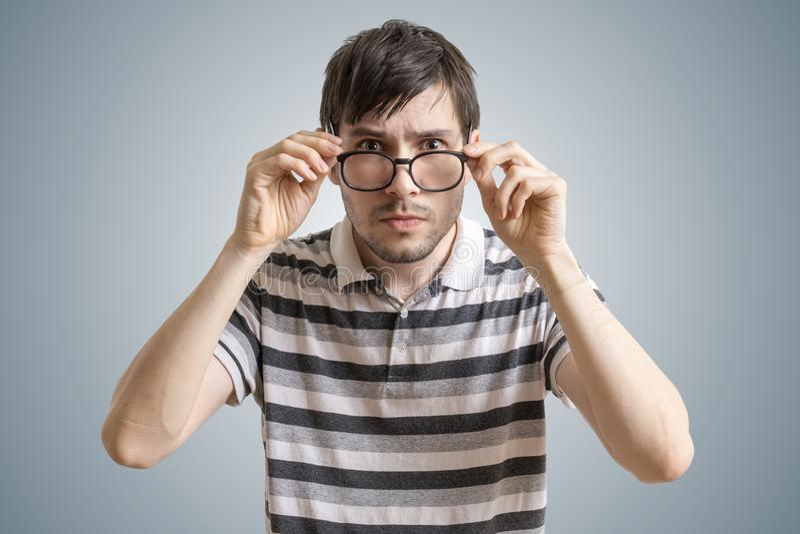 L'homme sceptique ou méfiant regarde vous et les verres émouvants photo stock