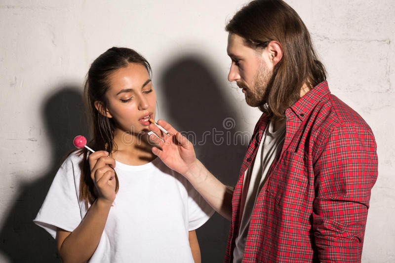 L'homme se tenant au-dessus du fond gris donnent la cigarette à l'amie photographie stock
