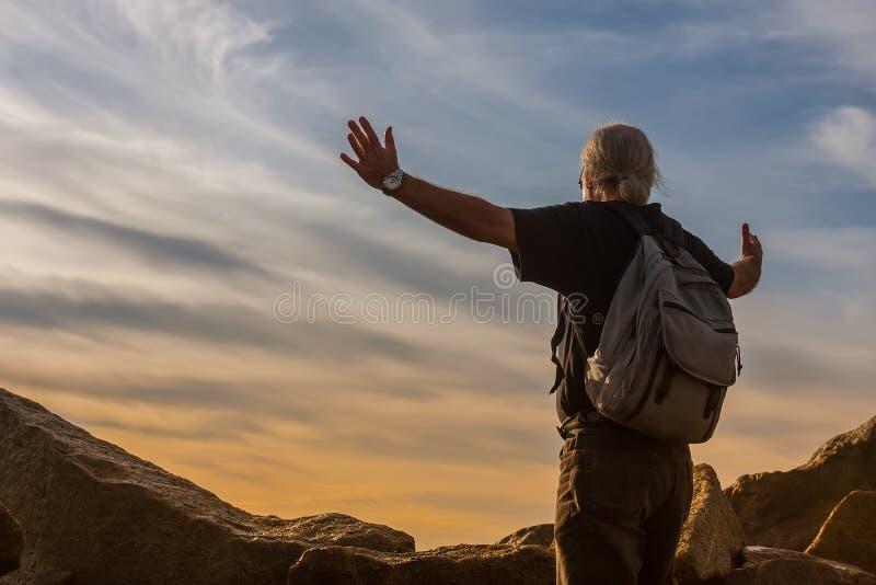 L'homme se tenant sur de grandes roches embrasse le monde avant lui image libre de droits