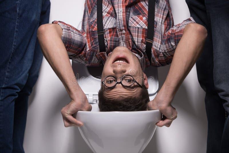 L'homme se tient à l'envers sur la cuvette des toilettes photographie stock libre de droits